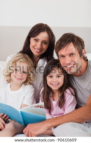 Portrait of a happy family reading a book in a bedroom - stock photo
