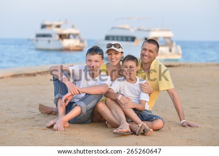 Portrait of a happy family sitting at beach in summer - stock photo