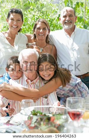 Portrait of a happy family with joyful children hugging their grandfather during a sunny summer day on a holiday home green garden while having lunch outdoors. Family relaxing on vacation, lifestyle. - stock photo