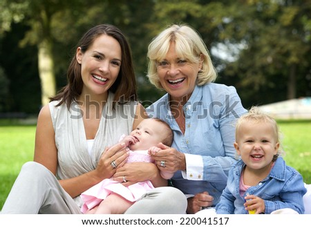 Portrait of a happy family with mother, children and grandmother outdoors - stock photo
