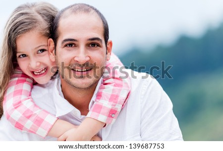 Portrait of a happy father and daughter smiling outdoors - stock photo