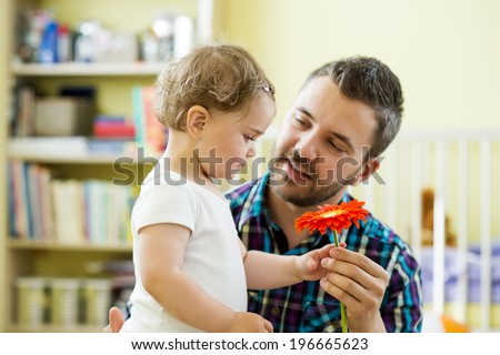 Portrait of a happy father with flower and his little daughter - stock photo