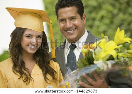 Portrait of a happy female graduate with flowers and father outside - stock photo