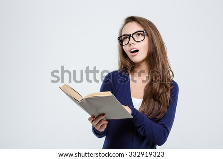 Portrait of a happy female student holding book and looking up at copyspace isolated on a white background - stock photo