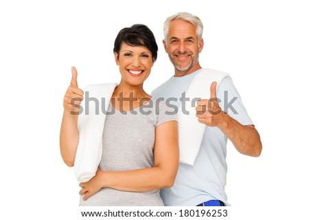 Portrait of a happy fit couple gesturing thumbs up over white background - stock photo