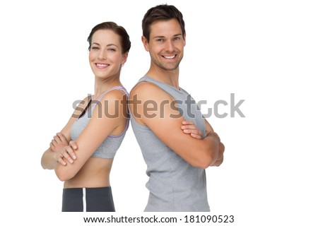 Portrait of a happy fit young couple with hands crossed over white background - stock photo
