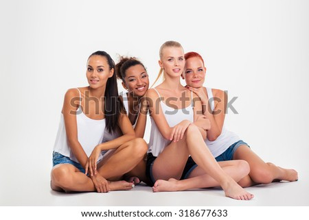 Portrait of a happy four multi ethnic women sitting on the floor isolated on a white background - stock photo