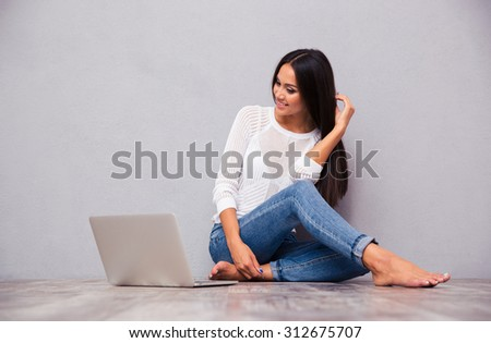 Portrait of a happy girl sitting on the floor with laptop on gray background - stock photo
