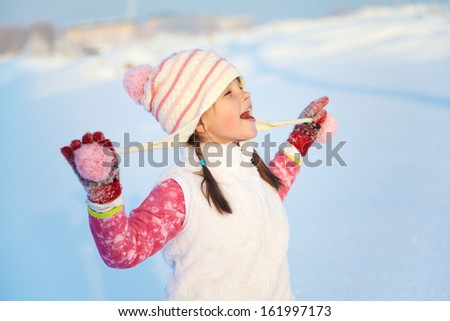 portrait of a happy girl walking around outdoors in the winter - stock photo