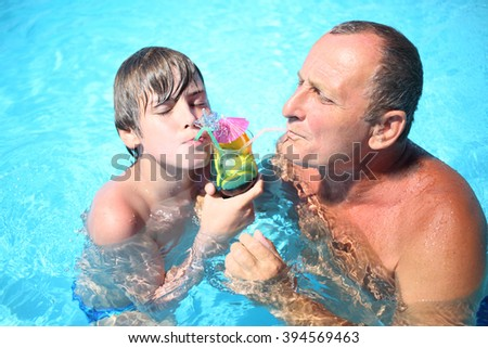 Portrait of a happy grandfather and young boy with a tropical cocktail at the swimming pool - stock photo