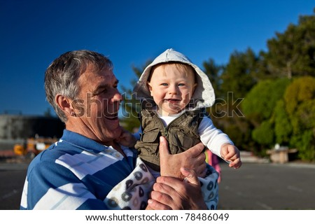 Portrait of a happy grandfather holding his grandson in his hands - stock photo
