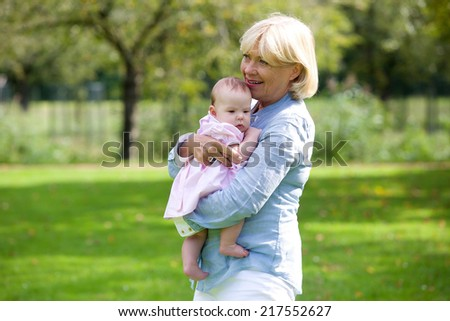 Portrait of a happy grandmother holding baby granddaughter - stock photo