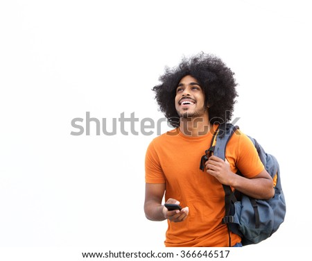 Portrait of a happy guy walking with mobile phone and bag - stock photo