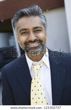 Portrait of a happy indian businessman wearing suit - stock photo