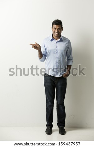 Portrait of a happy Indian man pointing his finger at an empty wall. Space for your message. - stock photo
