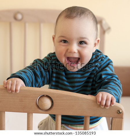 Portrait of  a happy laughing baby standing in a cot. - stock photo