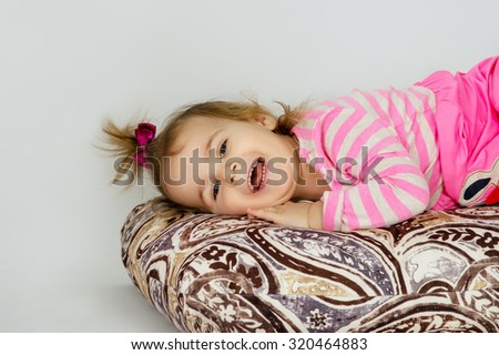 Portrait of a happy little girl lies - stock photo