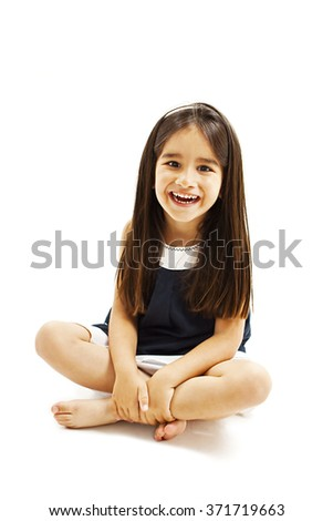 Portrait of a happy little girl sitting on floor. Isolated on white background - stock photo