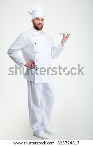 Portrait of a happy male chef cook standing with plate isolated on a white backgorund - stock photo