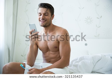 Portrait of a happy man holding toothbrush and using smartphone in bedroom - stock photo