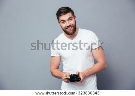 Portrait of a happy man holding wallet with money standing isolated on a white background - stock photo
