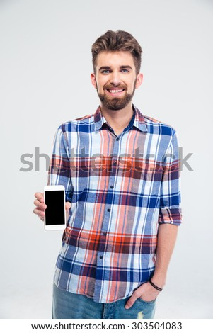 Portrait of a happy man presenting smartphone with blank screen isolated on a white background. Looking at camera - stock photo