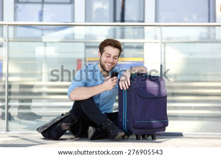 Portrait of a happy man sitting on floor at station reading text message  - stock photo