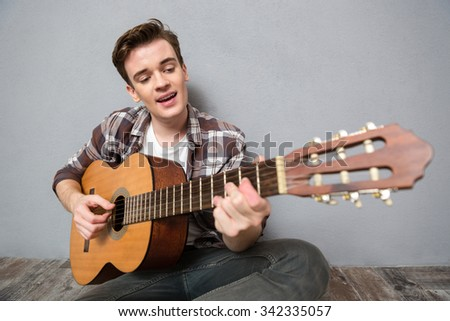 Portrait of a happy man sitting on the floor and playing on guitar over gray background - stock photo
