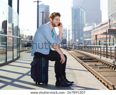 Portrait of a happy man talking on mobile phone waiting for train - stock photo
