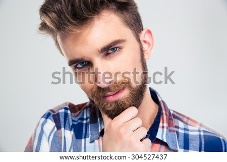 Portrait of a happy man touching his chin isolated on a white background. Looking at camera - stock photo
