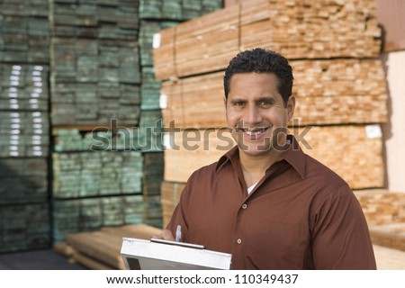 Portrait of a happy man with a clipboard in warehouse - stock photo