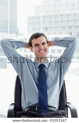 Portrait of a happy manager relaxing in his office - stock photo