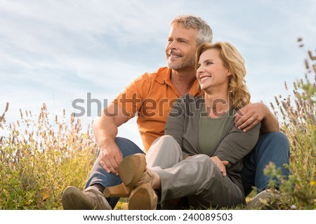 Portrait Of A Happy Mature Couple Sitting In Field And Contemplate The Future - stock photo