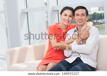 Portrait of a happy mature couple sitting on the sofa at home - stock photo