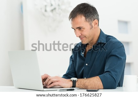 Portrait Of A Happy Mature Man Using Laptop - stock photo