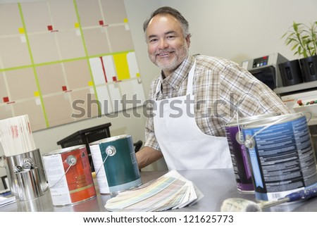 Portrait of a happy middle-aged sales clerk at counter with paint cans in hardware store - stock photo