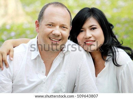 Portrait of a happy mixed race couple outside in the park - stock photo