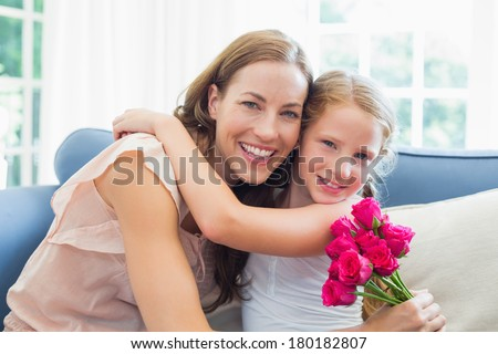 Portrait of a happy mother and daughter embracing with flowers in the living room at home - stock photo
