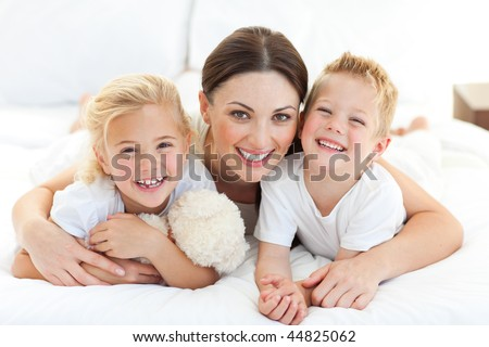 Portrait of a happy mother and her children lying on a bed - stock photo
