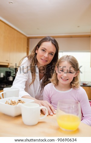 Portrait of a happy mother and her daughter having breakfast in a kitchen - stock photo