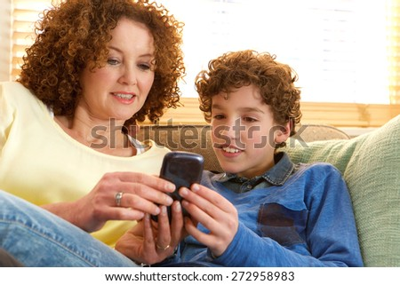 Portrait of a happy mother and son sitting on sofa at home looking at mobile device - stock photo