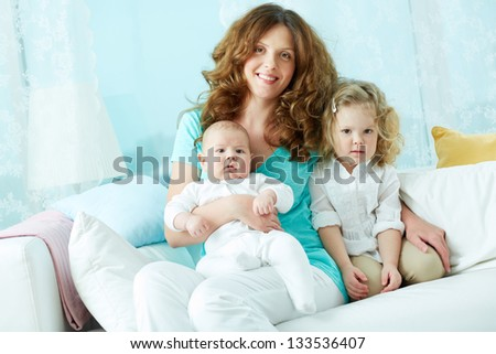 Portrait of a happy mother embracing her cute kids at home - stock photo