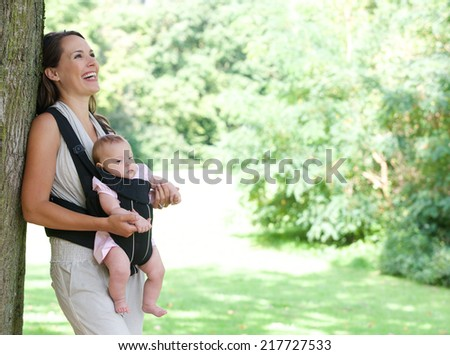 Portrait of a happy mother smiling in park with baby in sling - stock photo