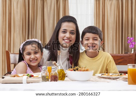 Portrait of a happy mother with her children having pizza at restaurant - stock photo