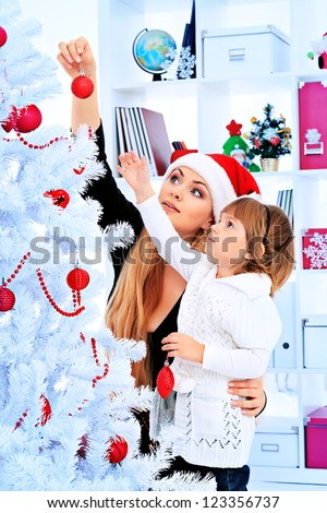 Portrait of a happy mother with her daughter decorating Christmas tree at home. - stock photo