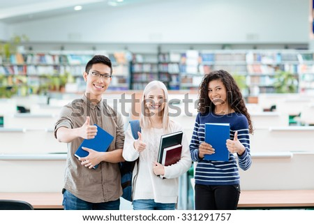 Portrait of a happy multi ethnic students standing in university library and showing thumbs up - stock photo