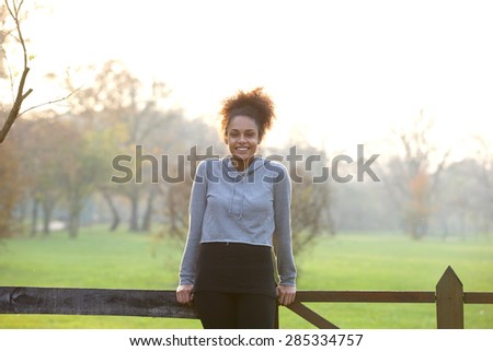 Portrait of a happy natural young woman standing outdoors - stock photo