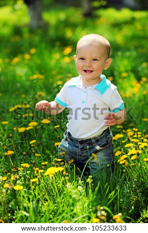 Portrait of a happy one-year old boy on a walk in a park - stock photo