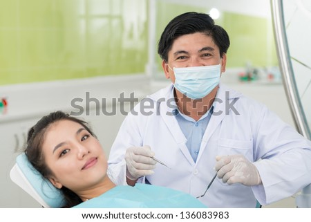 Portrait of a happy patient visiting an experienced dentist - stock photo