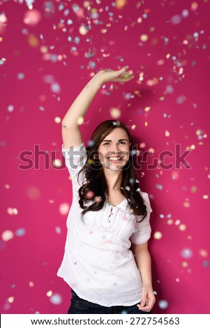 Portrait of a Happy Pretty Girl Raising One Arm on a Shower of Confetti While Looking Up. Isolated on a Fuchsia Background. - stock photo